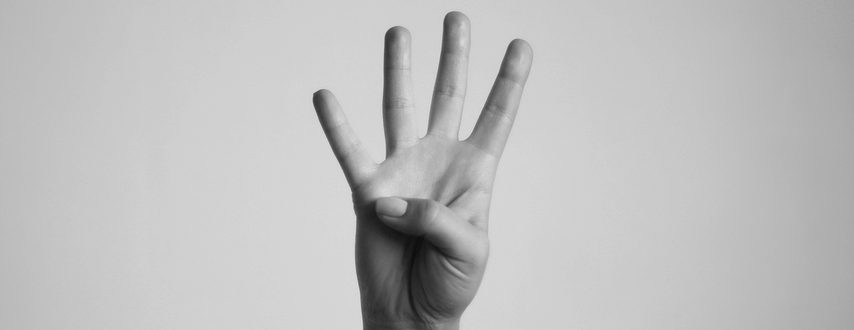 Black and white photo of a hand gesturing number 4 on blank background