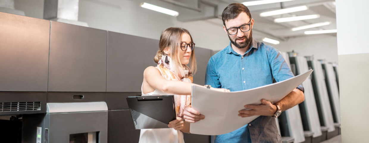 Woman and man talking in front of commercial printer