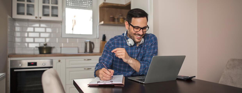 Man working remotely at home, using laptop, wearing headphones